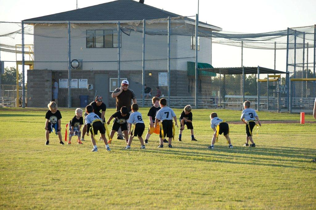 Two coaches with two boys flag football teams