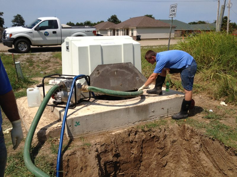 Picture of a public works employee operating a portable pump cleaning out a pumping station