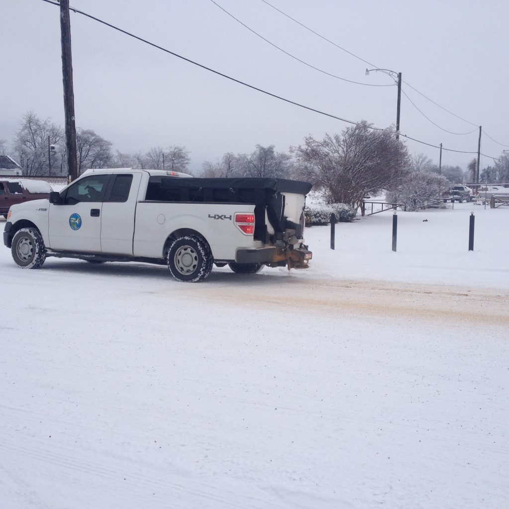 Picture of a Trumann Public Works truck spreading salt on a snowy road.