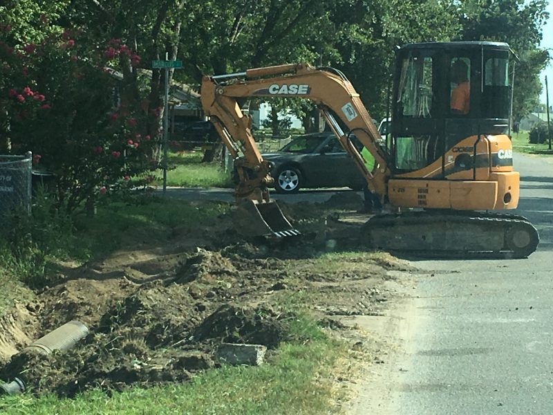 Picture of a mini-escavator installing drainage pipe in a road ditch.