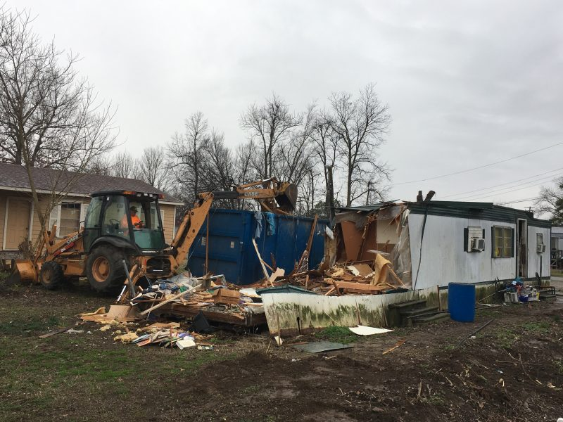 Demolishing an old trailer house with a backhoe